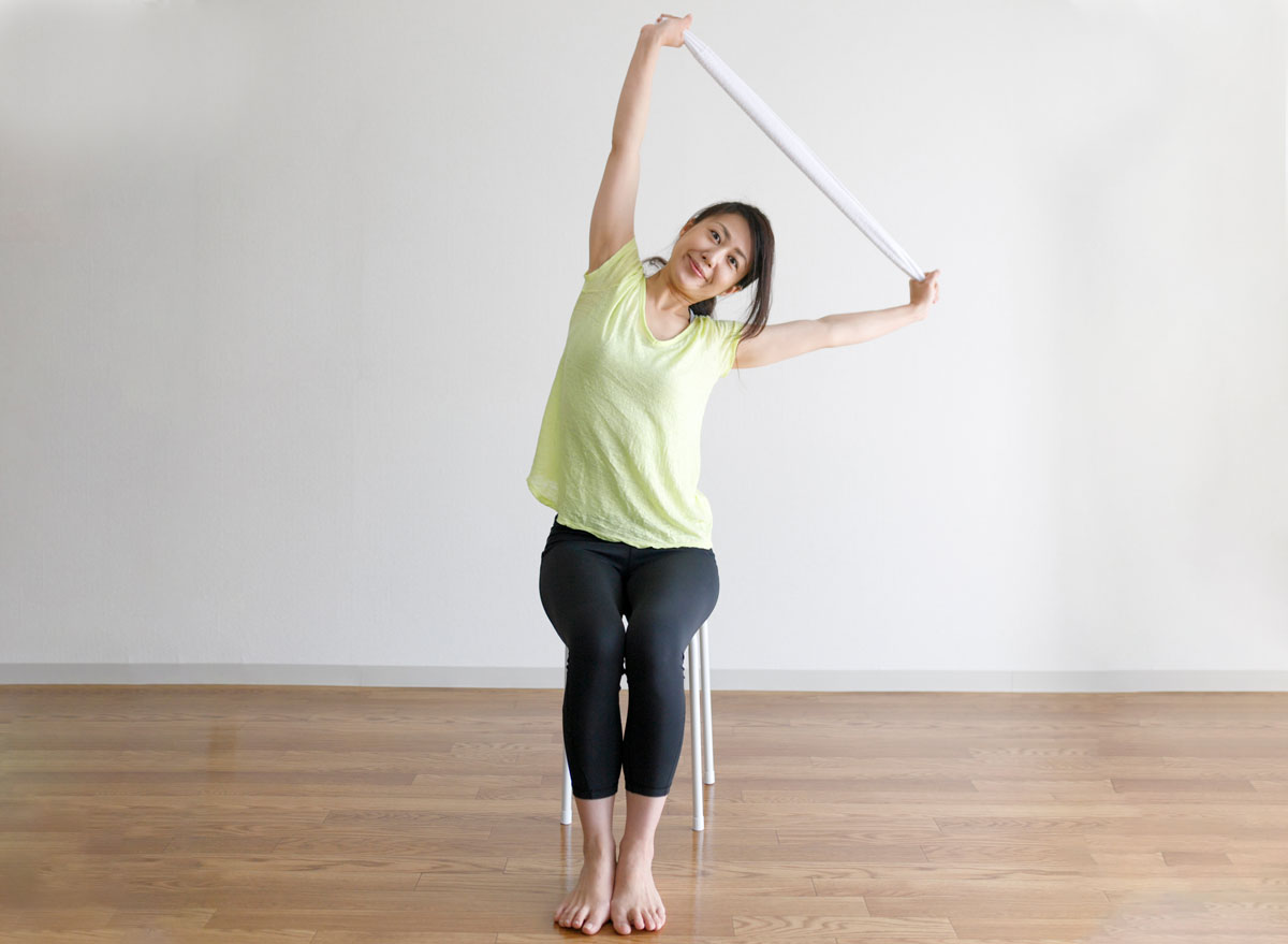 Woman doing exercises while sitting with a towel