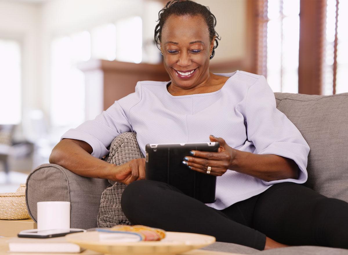 older black woman looking at tablet