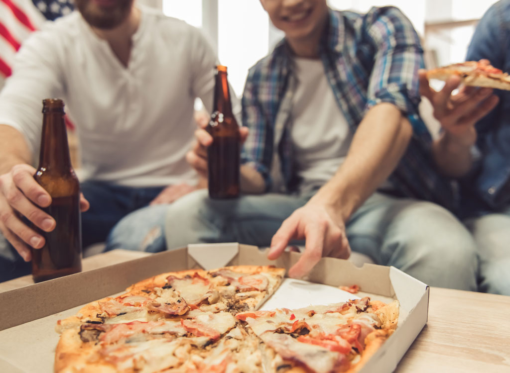 Man holding beer reaching for slice of pizza