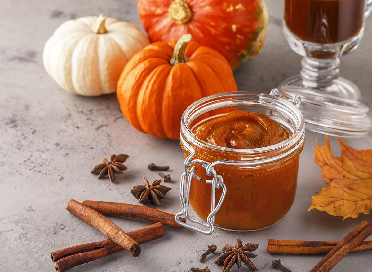 jar of homemade pumpkin butter with mini pumpkins and cinnamon sticks