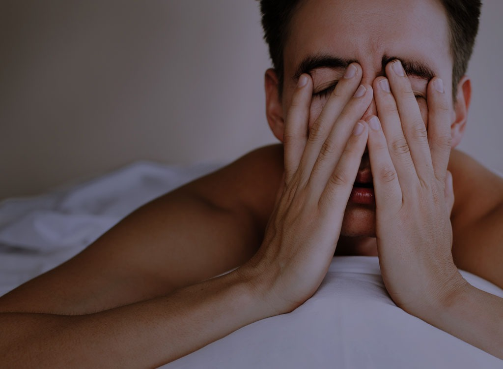 Man with hands over face in bed