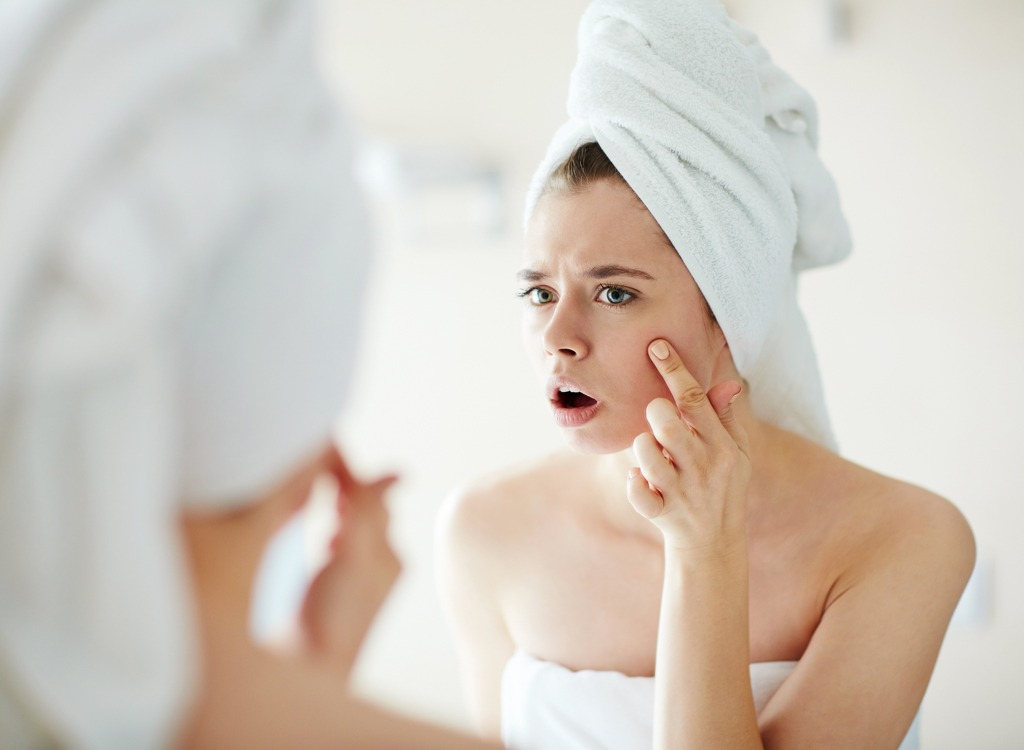 Woman looking at acne mirror
