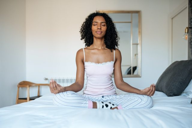 Woman sitting in a lotus position on the bed meditating