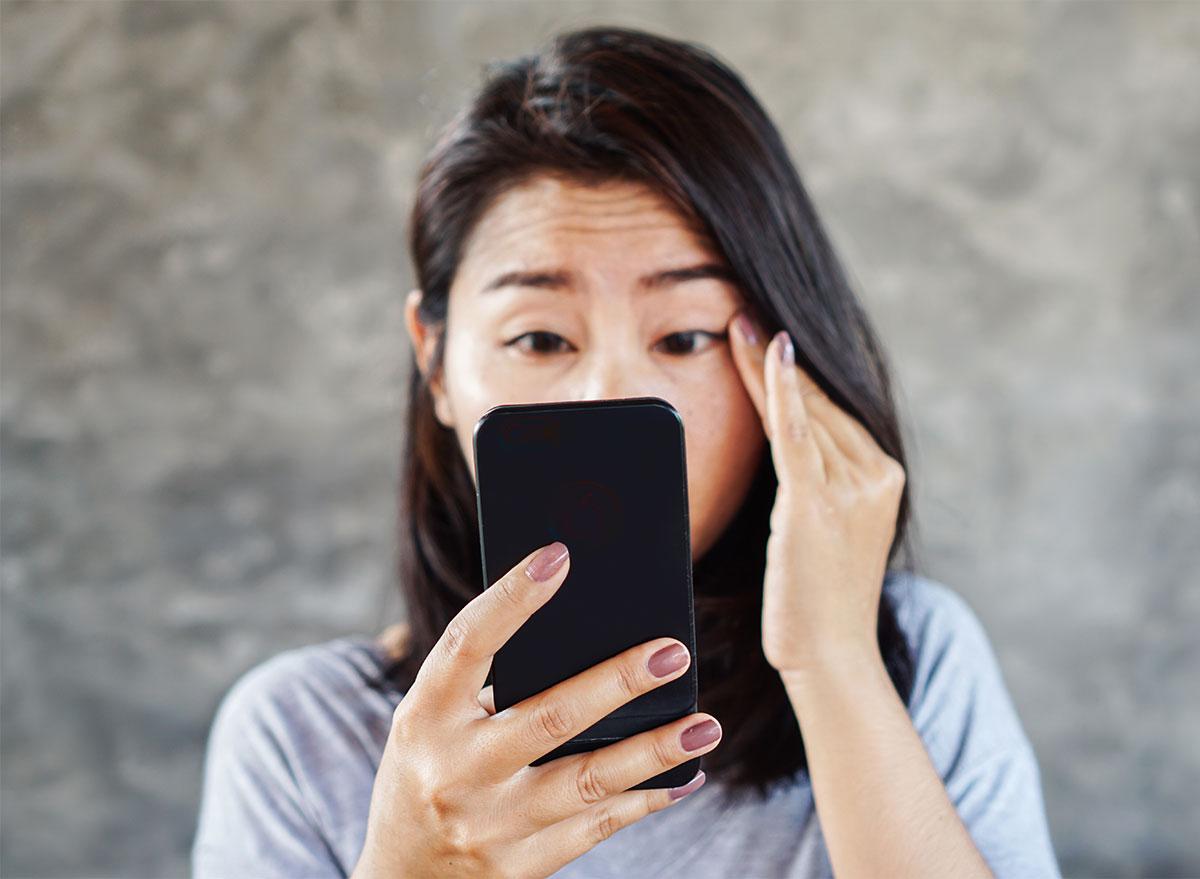 woman squinting at phone