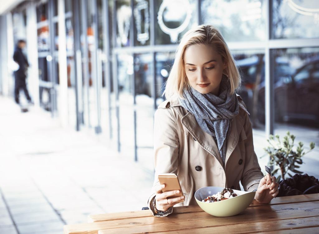 woman texting eating