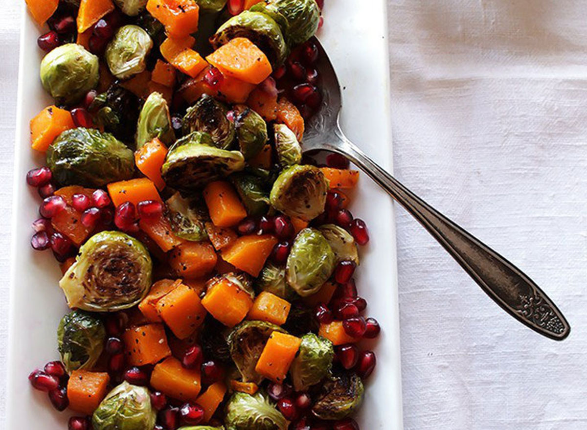Roasted brussels sprouts with butternut squash and pomegranates on a plate ready to be served