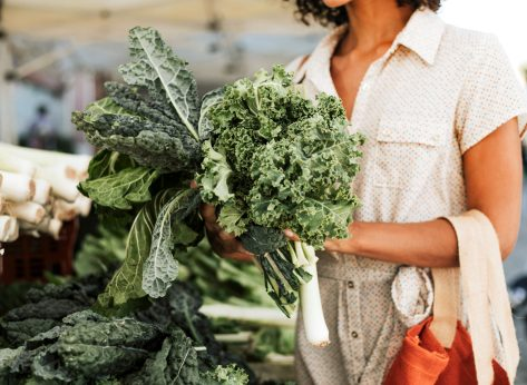 Woman picking out kale and leeks at a farmers market or grocery store