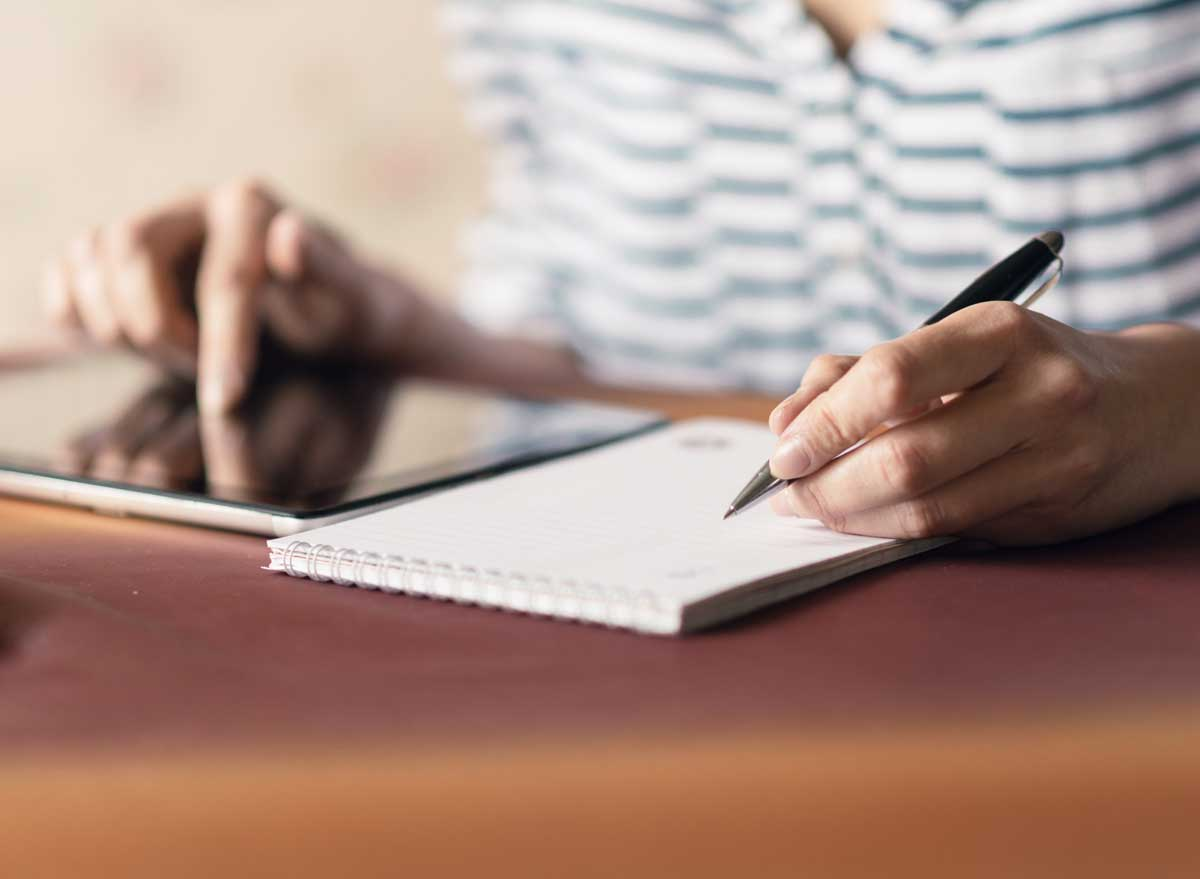 Man writing a to do list while also on his tablet computer