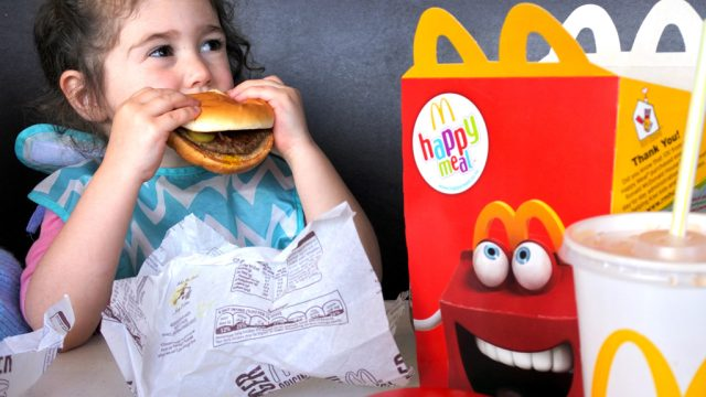 Child eating Mcdonalds happy meal