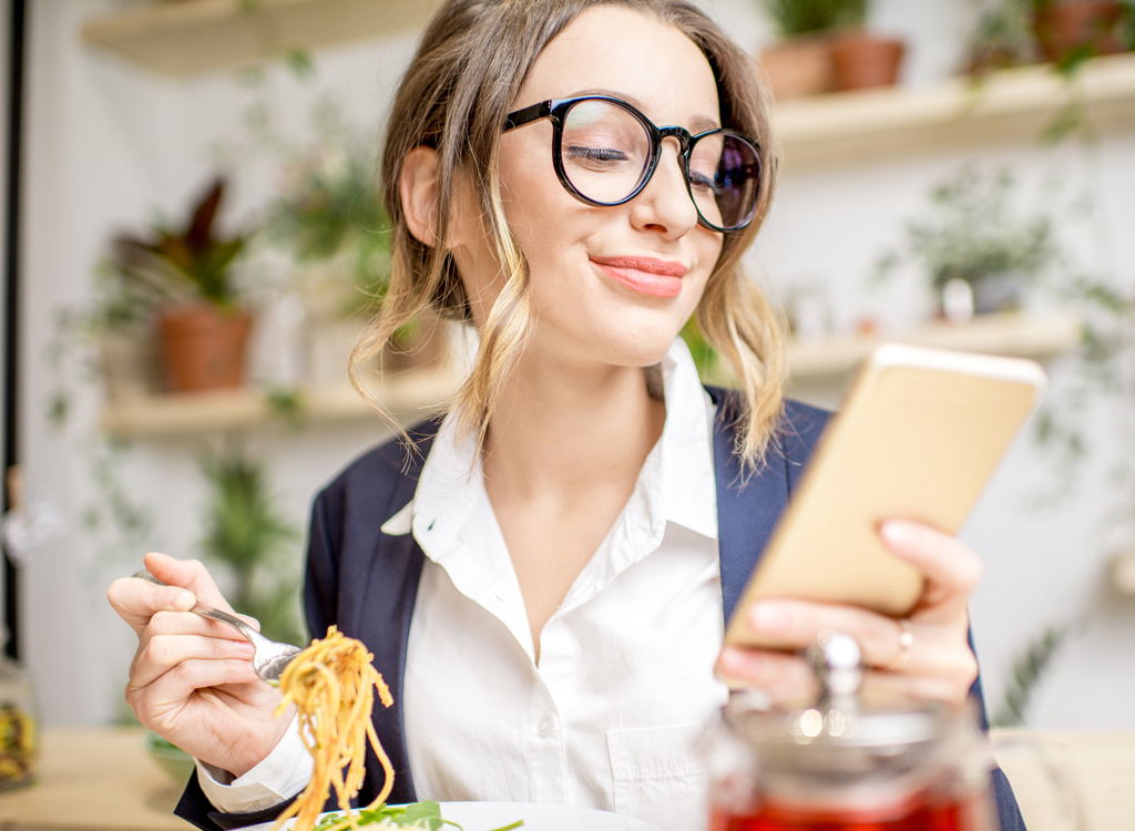 Woman eating with phone