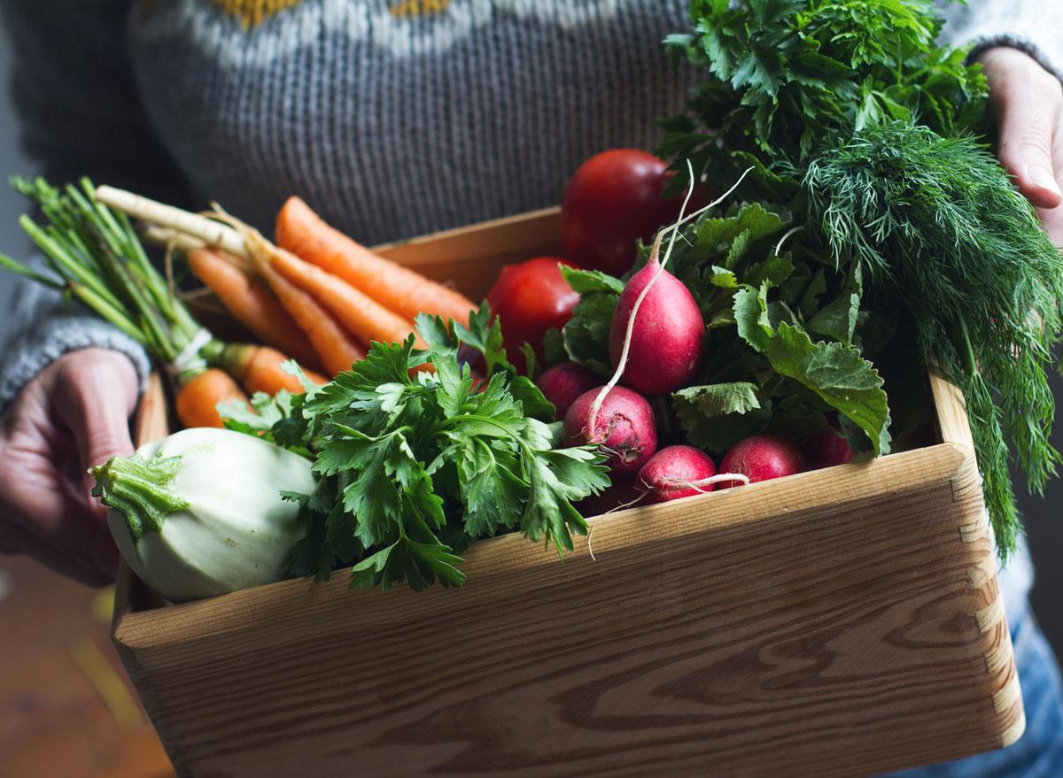 Woman holding csa box of organic fresh vegetables