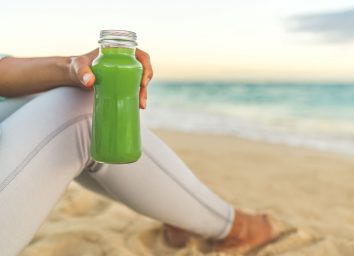 Woman holding green juice beach