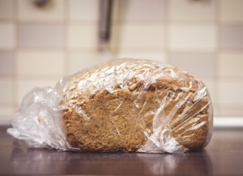 Loaf of bread on kitchen counter in plastic bag