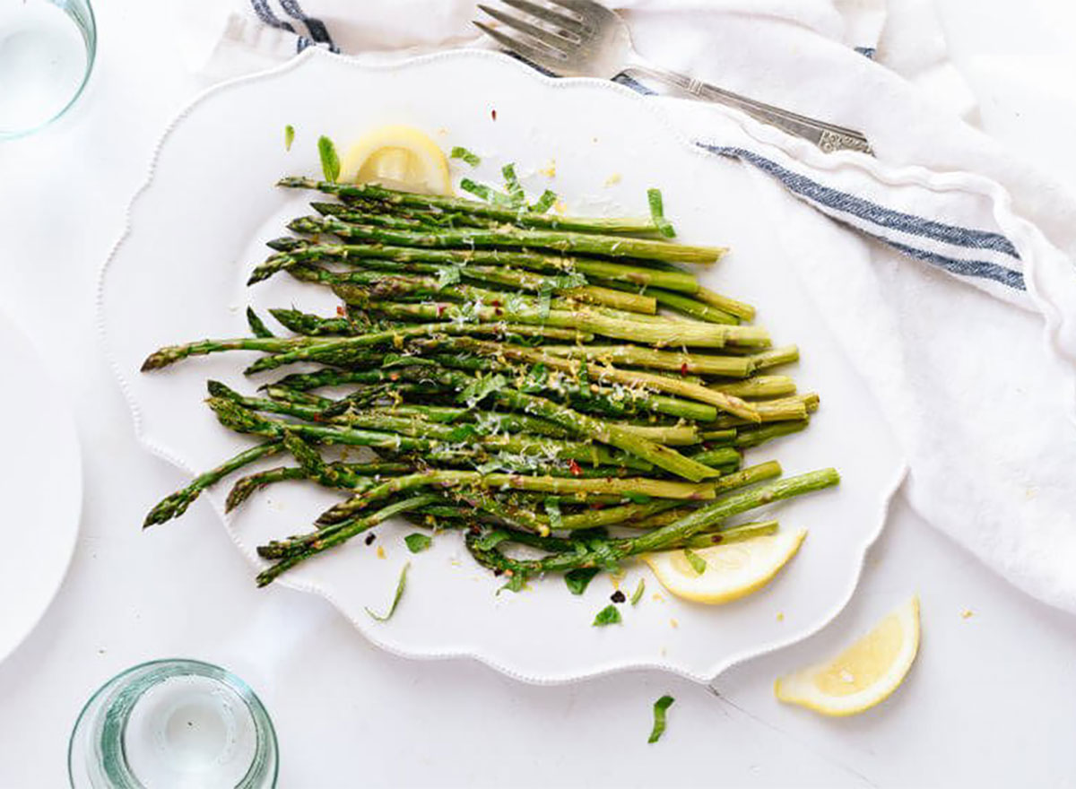 roasted asparagus on serving plate with lemon wedges
