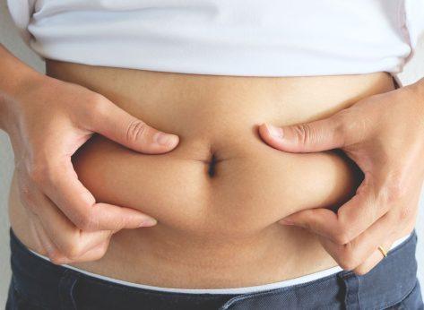Woman grabbing belly fat