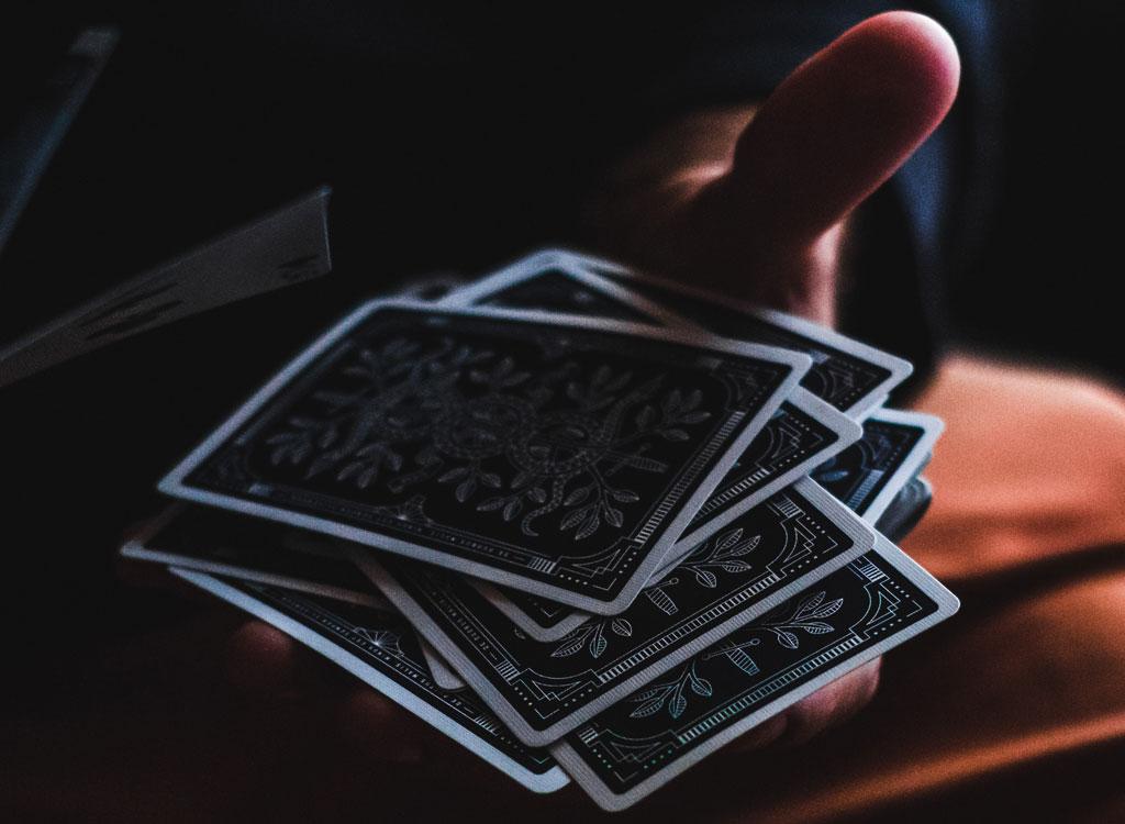 Man holding playing cards dark