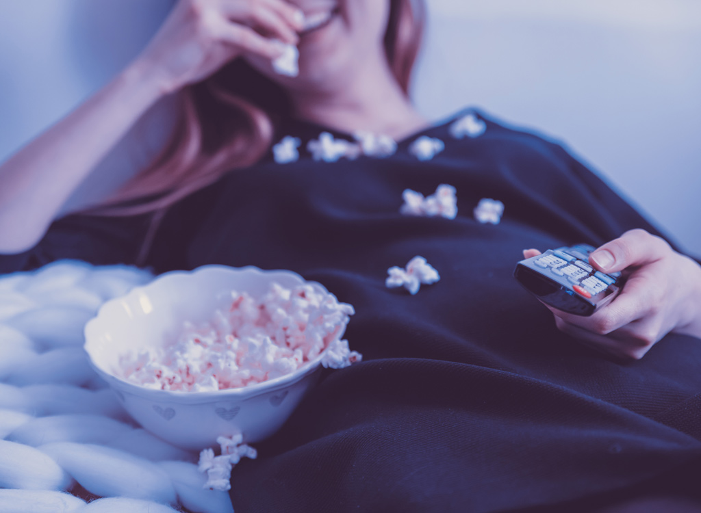 Woman eating popcorn by TV