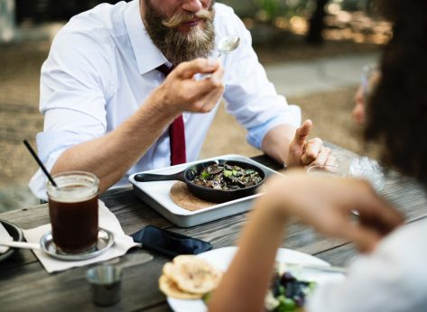Man eating from cast iron skillet at table