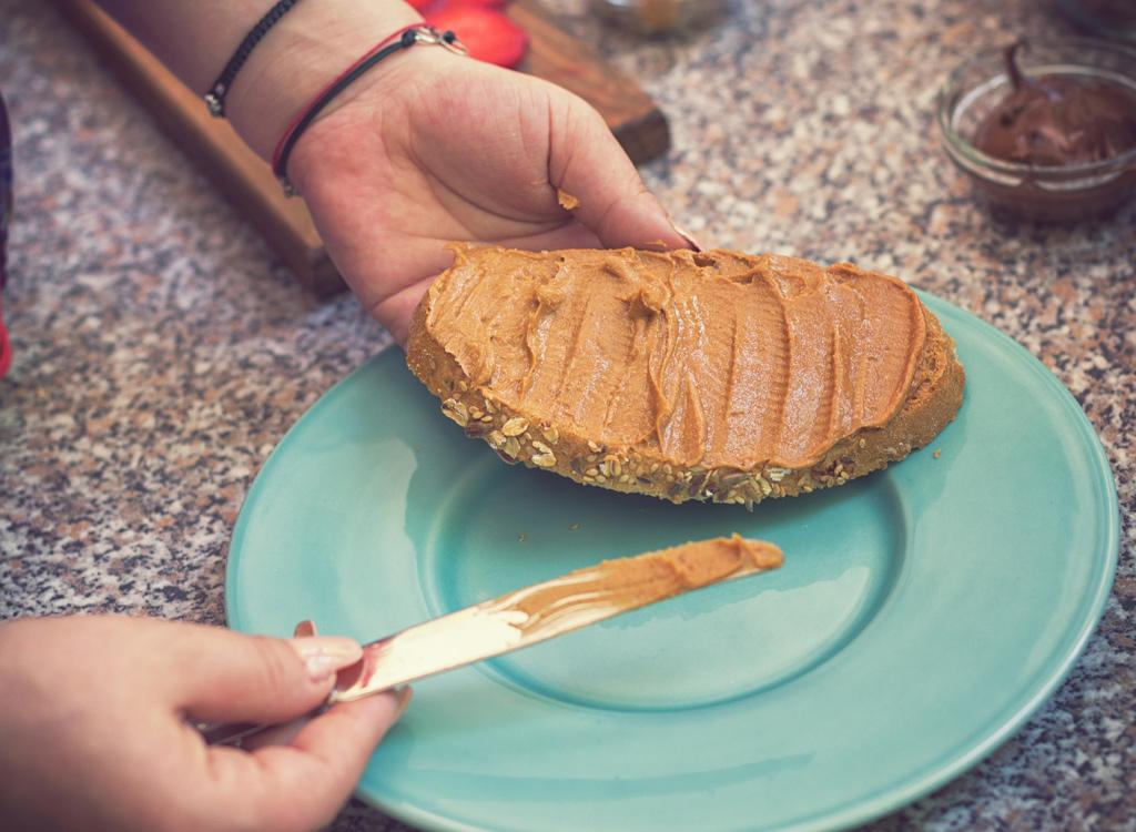 Woman spreading peanut butter on bread