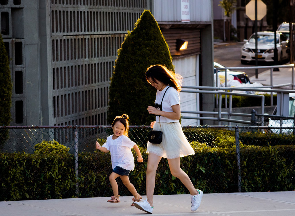 Woman and daughter running uphill