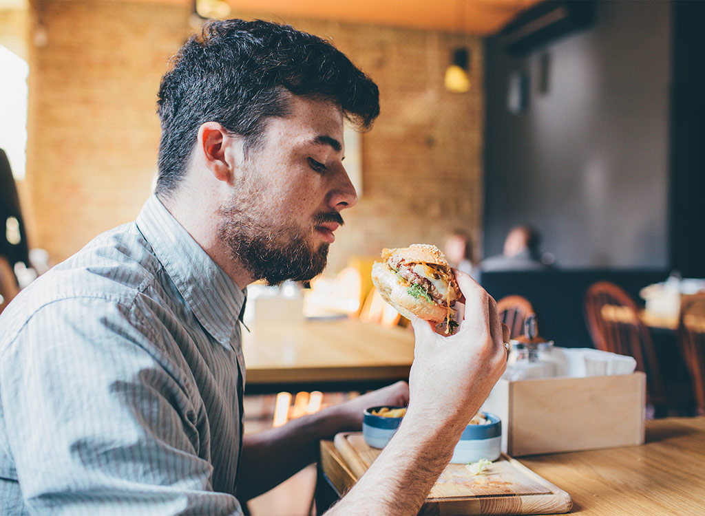 Guy eating at fast-food restaurant