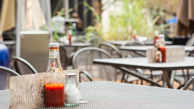Ketchup glass bottle on table at restaurant