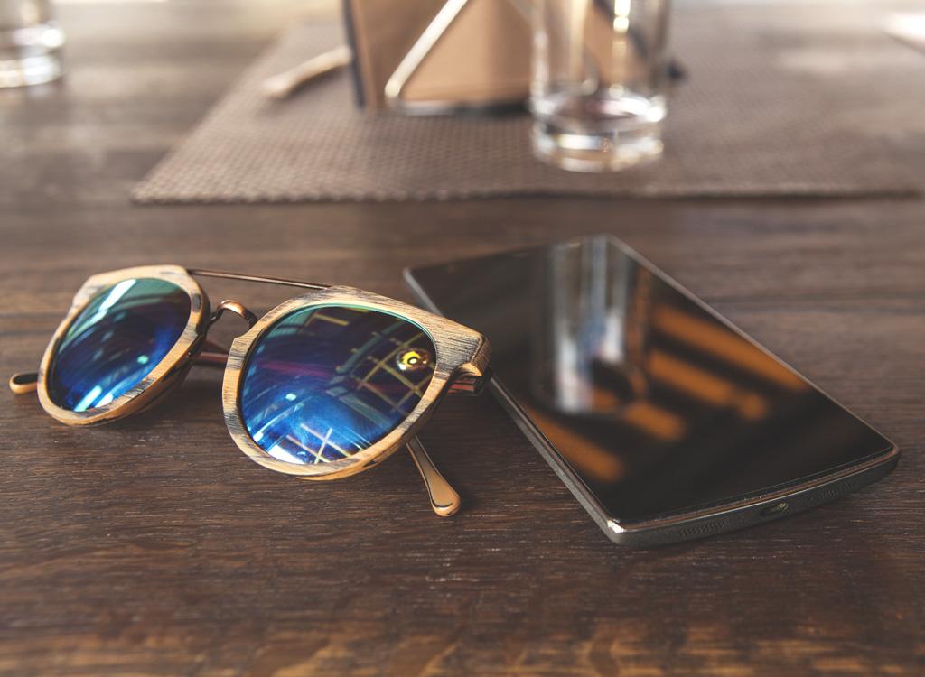 Phone sunglasses left on table
