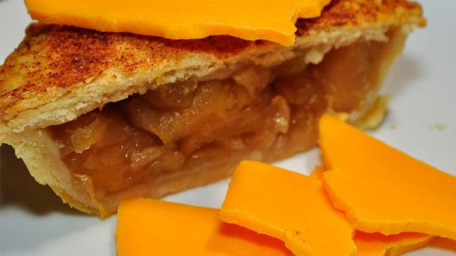 half apple pie with cheese slice on top