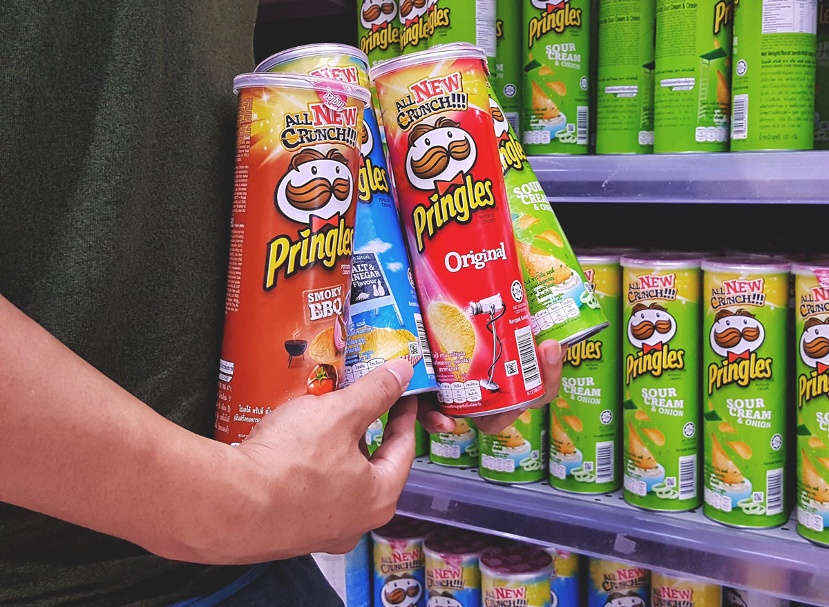 Buy one get one free deal grocery store deal man holding 4 cans pringles