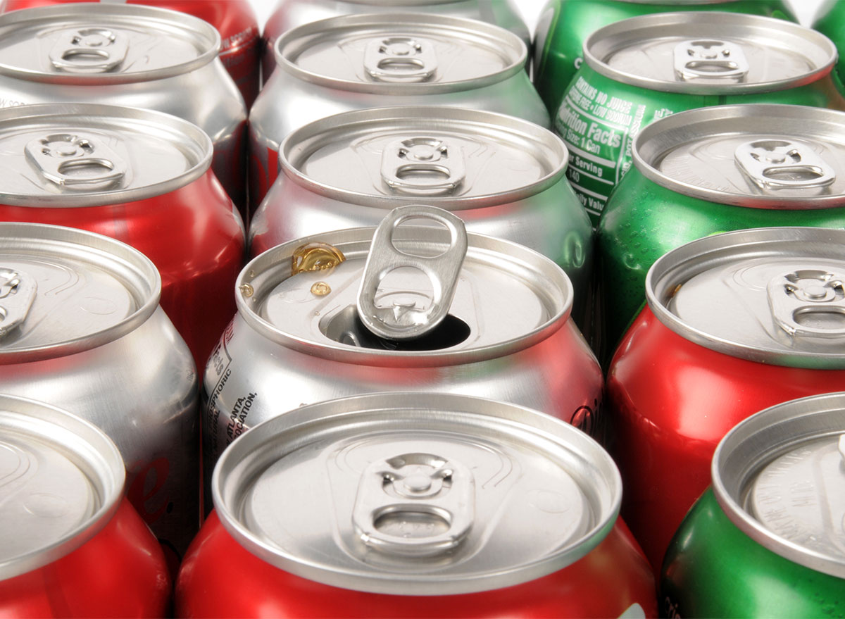 rows of soda cans with one can open