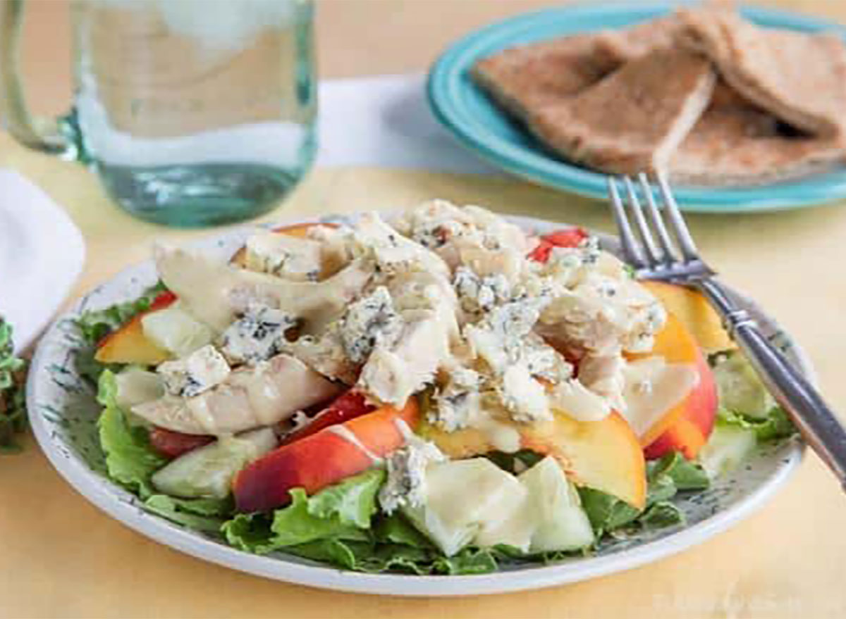 peach tomato chicken blue cheese salad on plate with fork and bread
