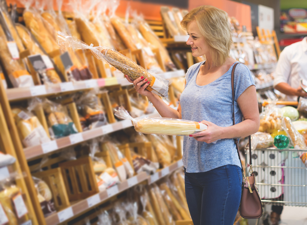Woman picking up loaf bread