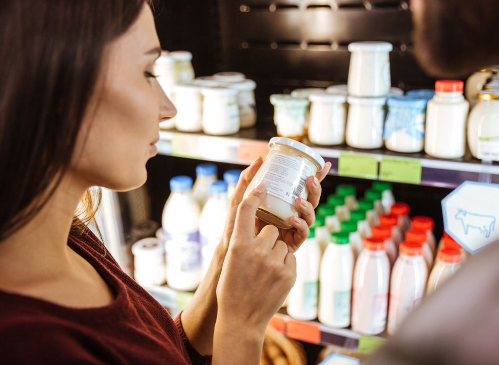 Woman picks up yogurt from grocery store shelf