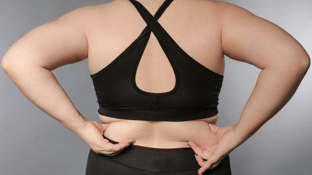 woman in sports bra touching back fat