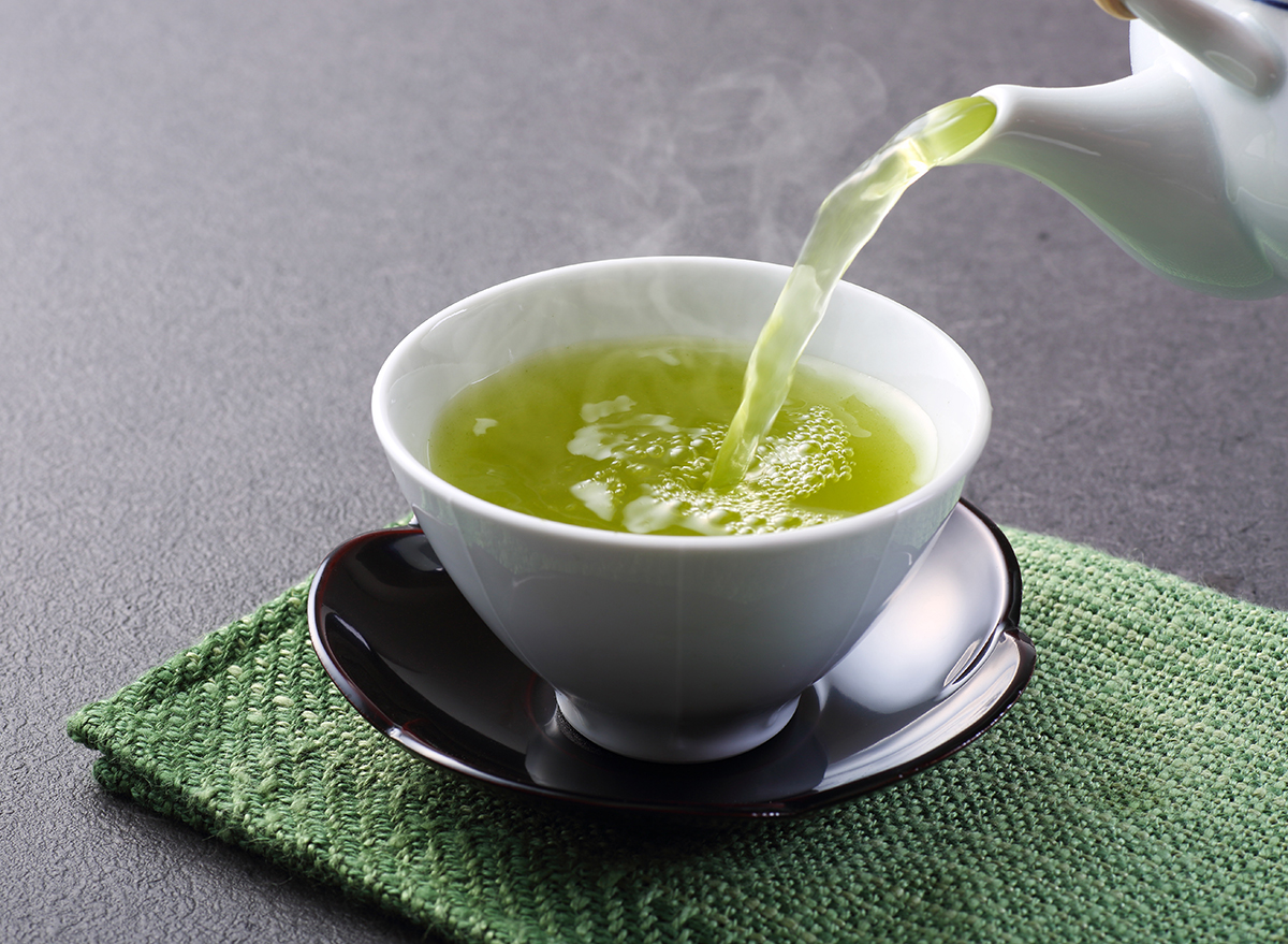 green tea being poured into white teacup