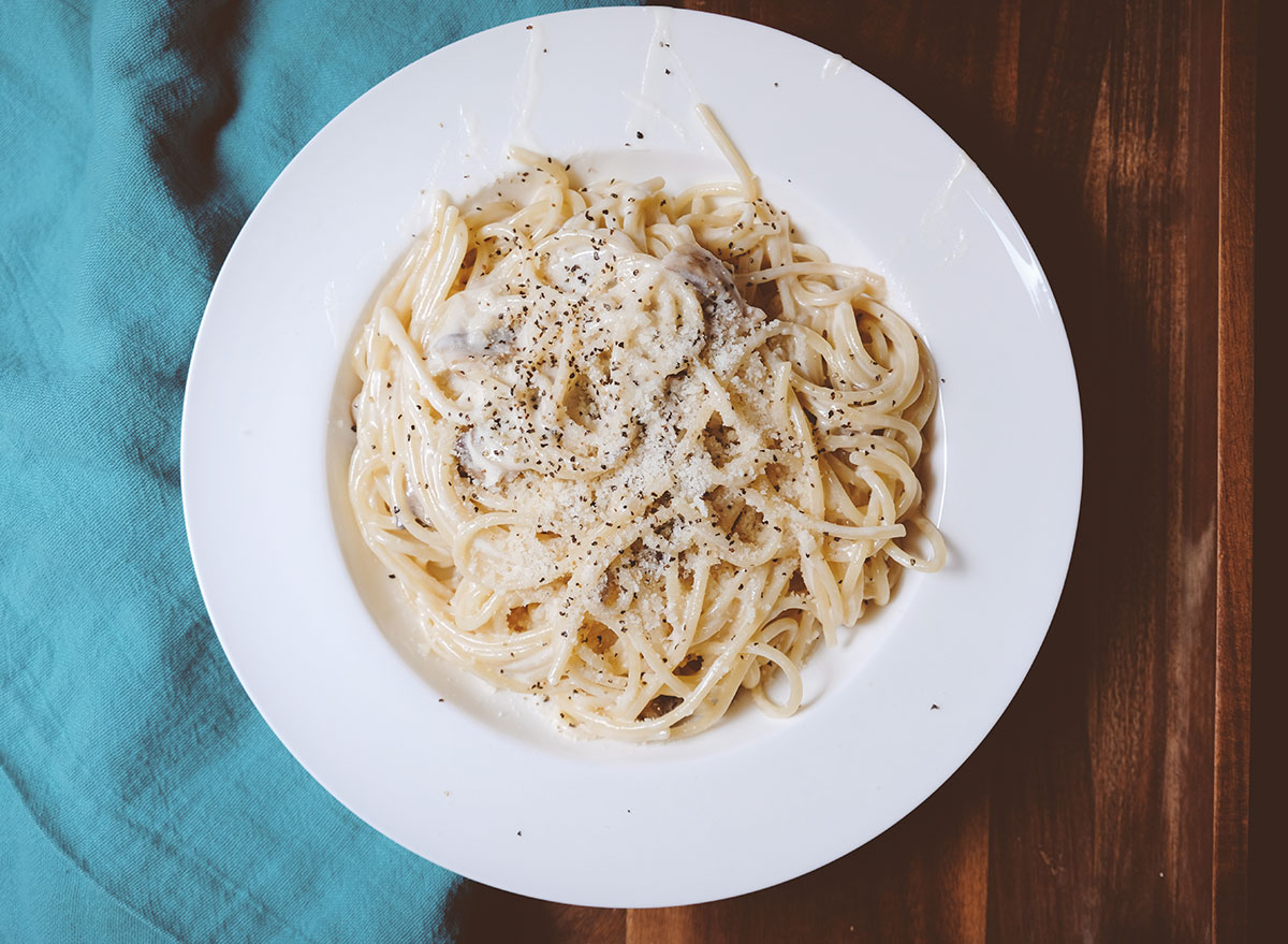bowl of alfredo pasta with cheese and pepper