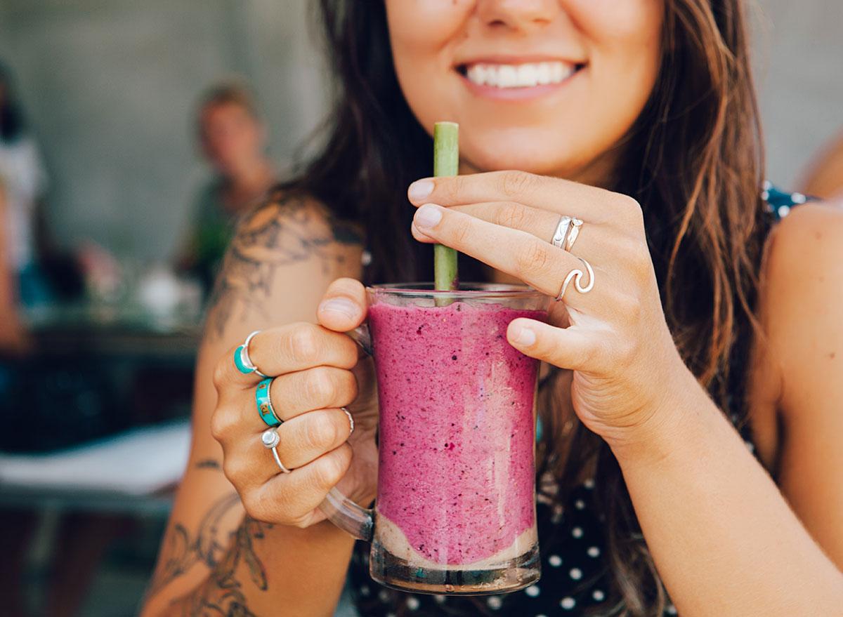 girl holding smoothie at bar