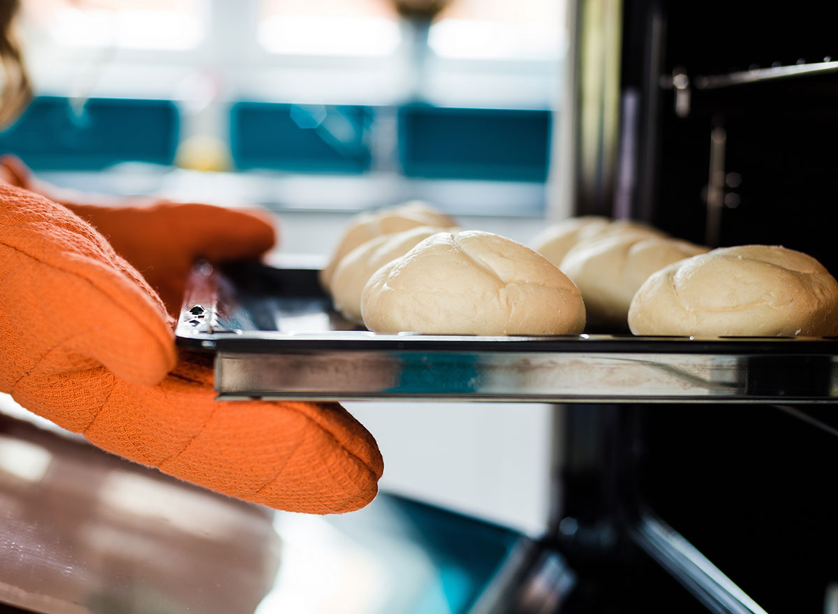 Gloves holding pan into oven