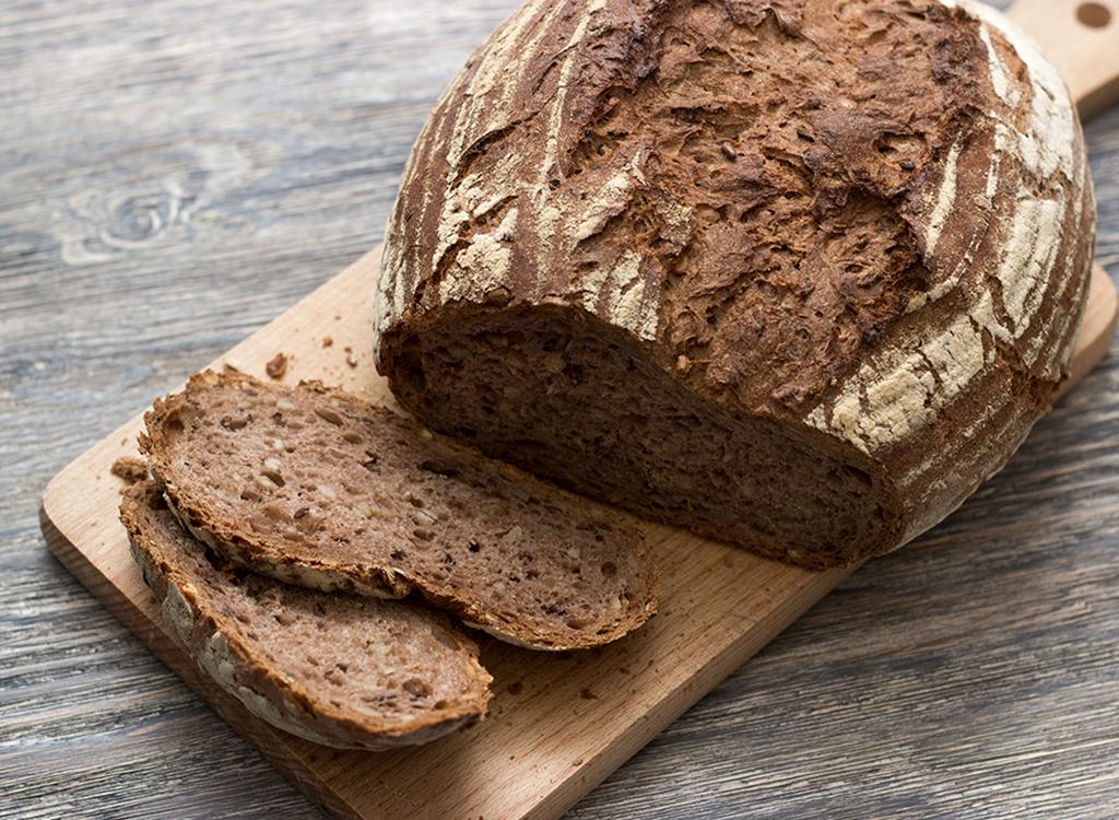 loaf of crusty brown bread on cutting board