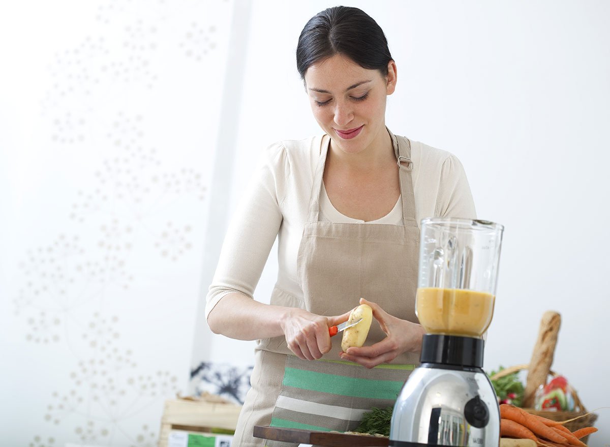 woman peeling potato for soup in blender
