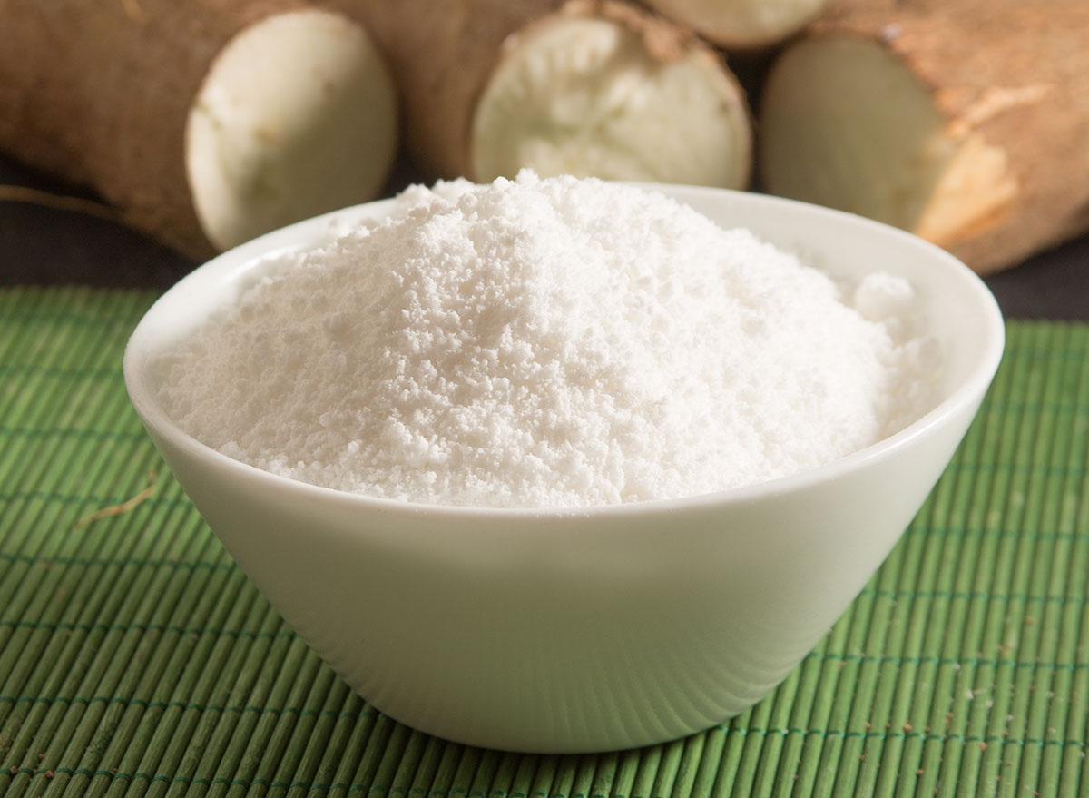 Cassava flour in bowl with roots