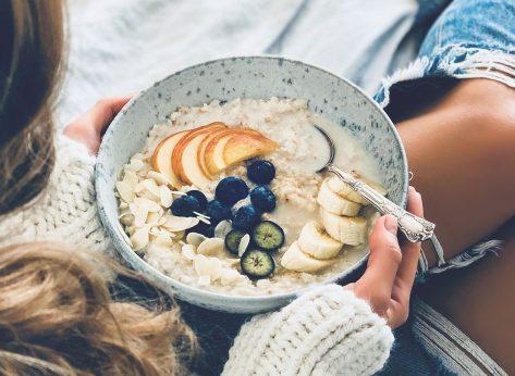 Woman eating oatmeal breakfast fresh fruit