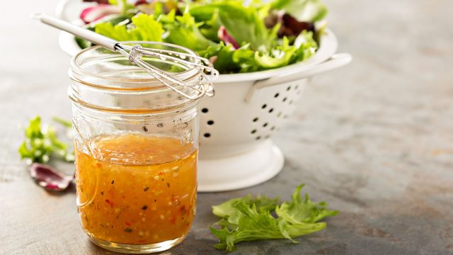 bottle of italian dressing with salad
