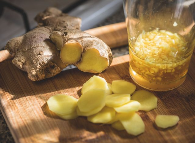 Sliced ginger and ginger root on wooden cutting board