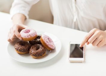 Woman counting calories on her phone for a junk food dessert treat doughnut