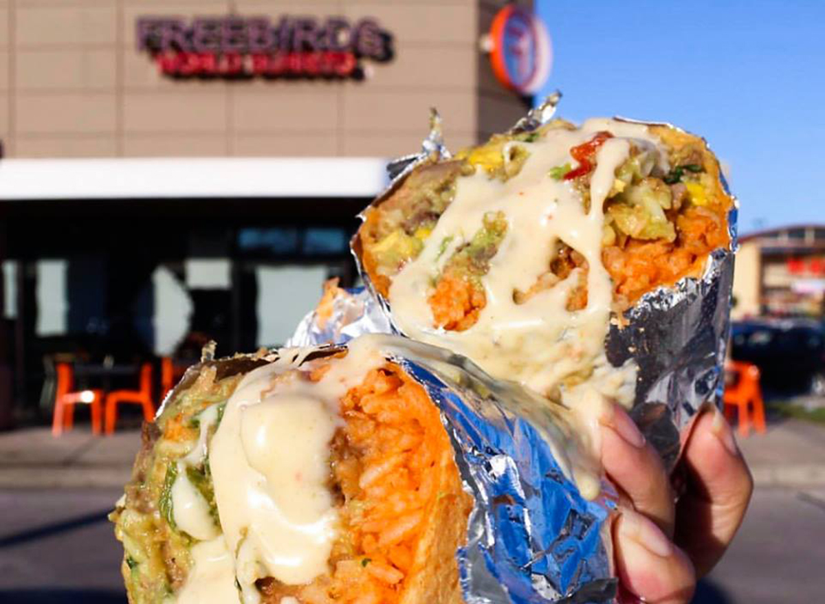 Burrito-split-in-half-in-foil-in-front-of-freebirds-restaurant