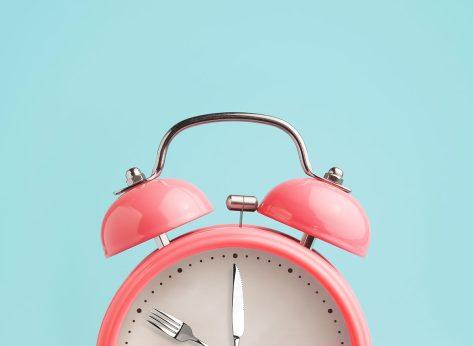 pink alarm clock on blue background