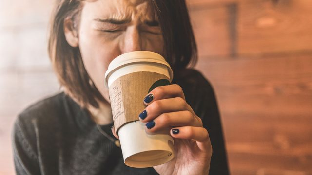 Girl cringing at hot coffee cups