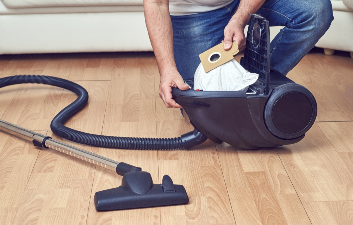 Man taking out a full dust bag from a vacuum cleaner.