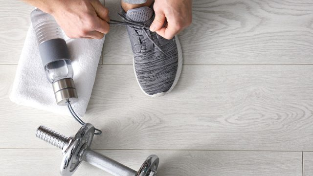 Man tying shoe before workout
